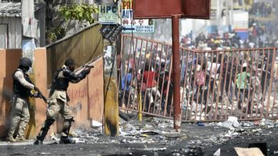 A member of the Haitian police points his gun at people to discourage looting and disperse fresh protests in a commune of the capital AFP Photo HECTOR RETAMAL