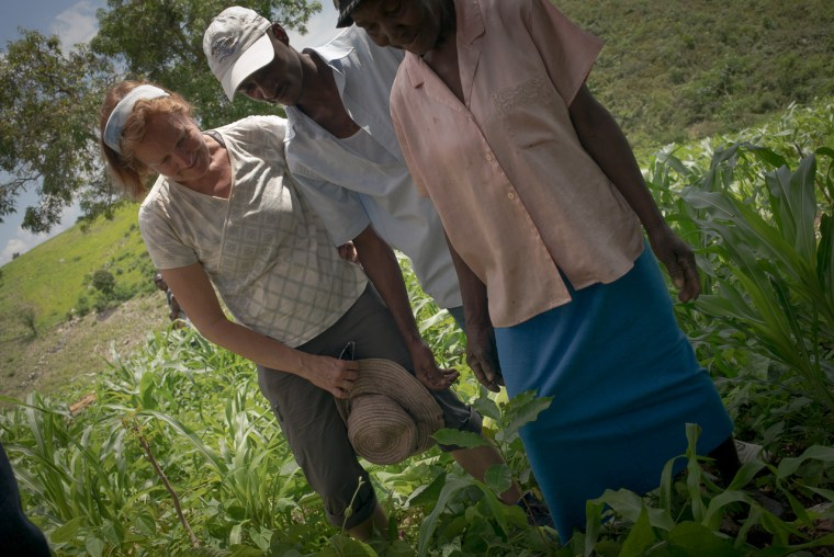 Professor Deborah McGrath, Agronimist Bosque Wupui and Madame Josephine Exana admire her first planting of a coffee sapling. May 26, 2014.