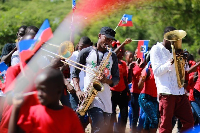 Flag-waving revelers and musicians during a Haitian celebration — Bailey Torres from Unsplash
