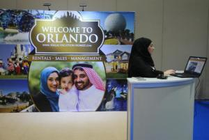 an exhibitor works at an American Halal Vacation Homes booth at The World Halal Travel Summit & Exhibition in Abu Dhabi, United Arab Emirates. Halal tourism is growing as the hospitality industry seeks ways to better serve Muslim travelers, from providing alcohol-free venues to swimming areas that are segregated by gender. (AP Photo/Kamran Jebreili)