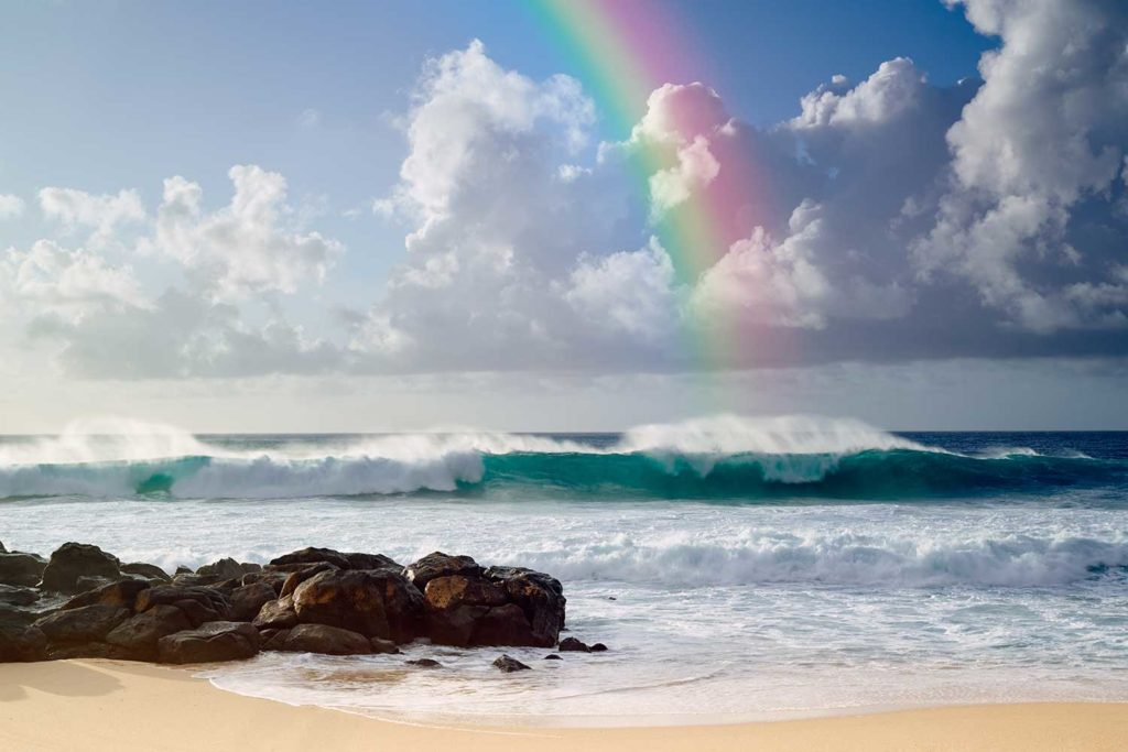 ocean shoreline with rock and rainbow