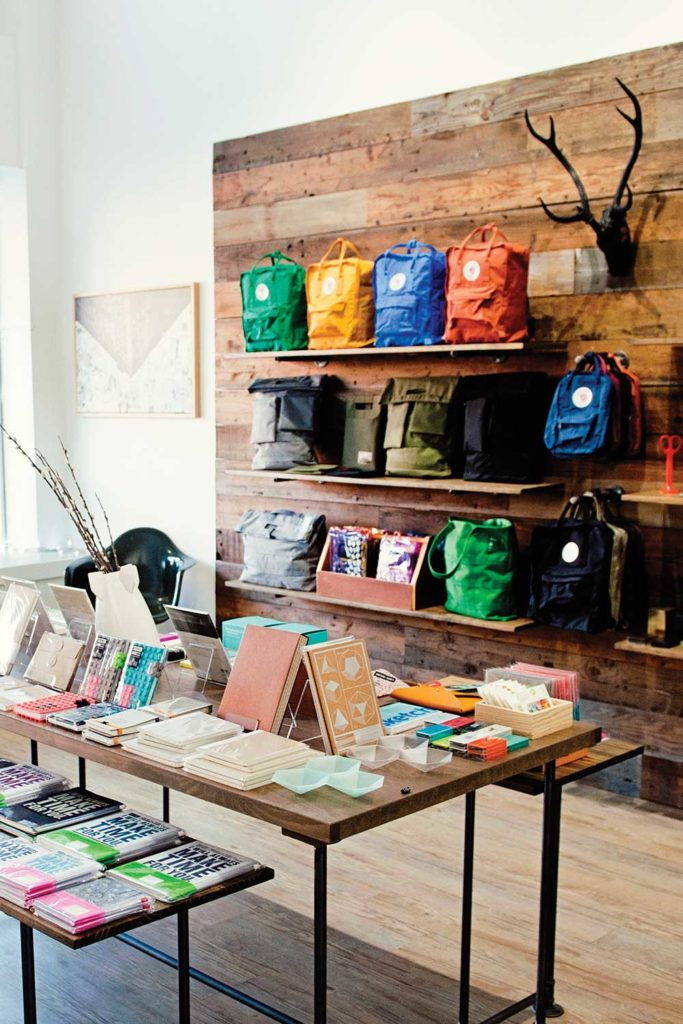 store display with journals on table and colorful backpacks on wall shelves
