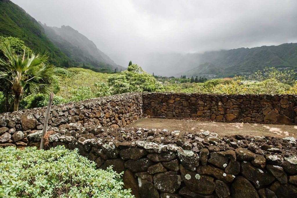stone wall overlooking green hills and misty mountain view