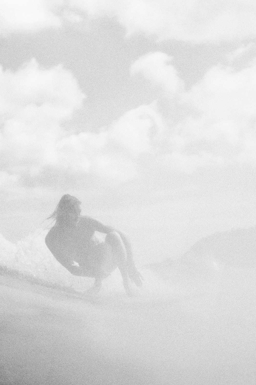 black and white photo of man riding a surfboard