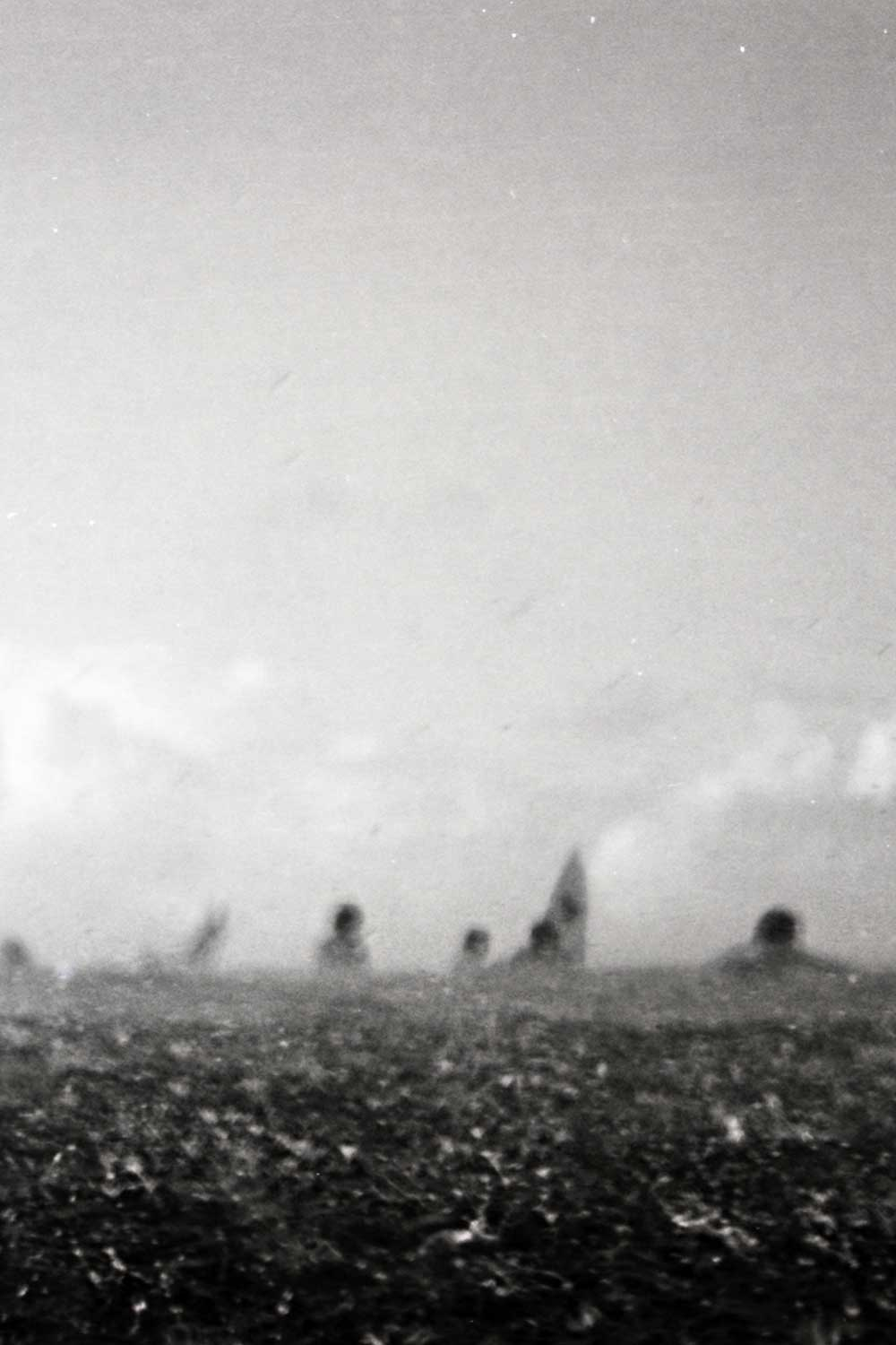 blurry black and white photo of surfers in the ocean