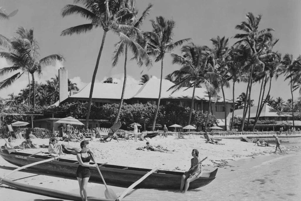 black and white photo of women sitting on canoe under hau trees at Kawehewehe Beach