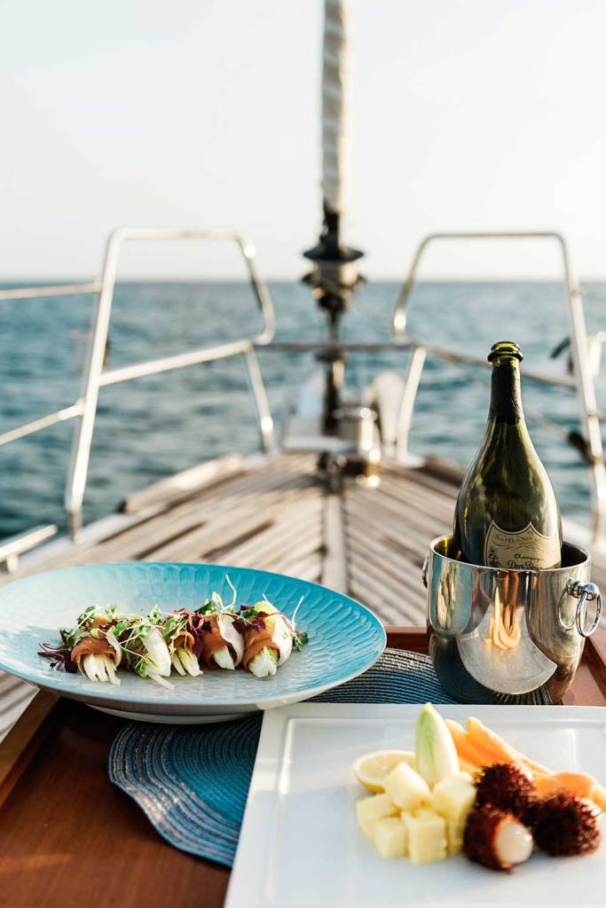 view of sushi plate, wine bottle and fruit plate on deck of yacht overlooking the ocean