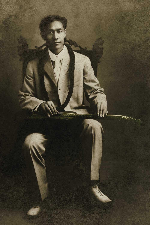 black and white photo of Joseph Kekuku with steel guitar on lap