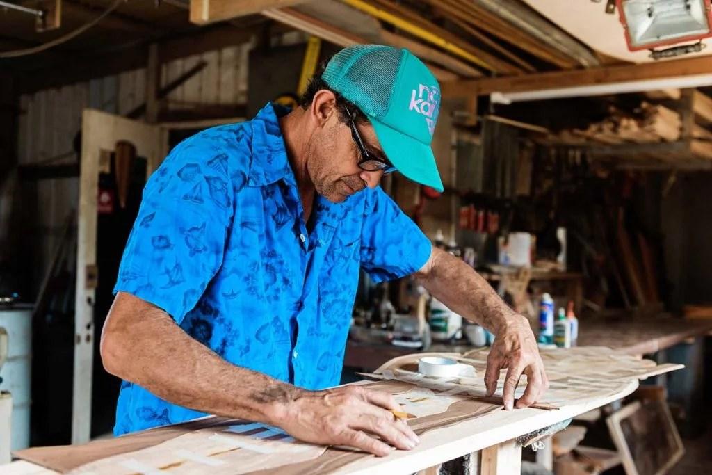 Leleo Kinimaka working on inlay wood surfboard