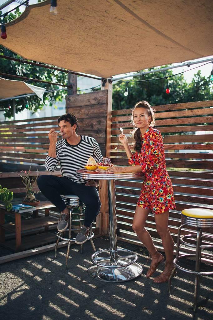 man and woman enjoying dessert on restaurant patio under umbrella