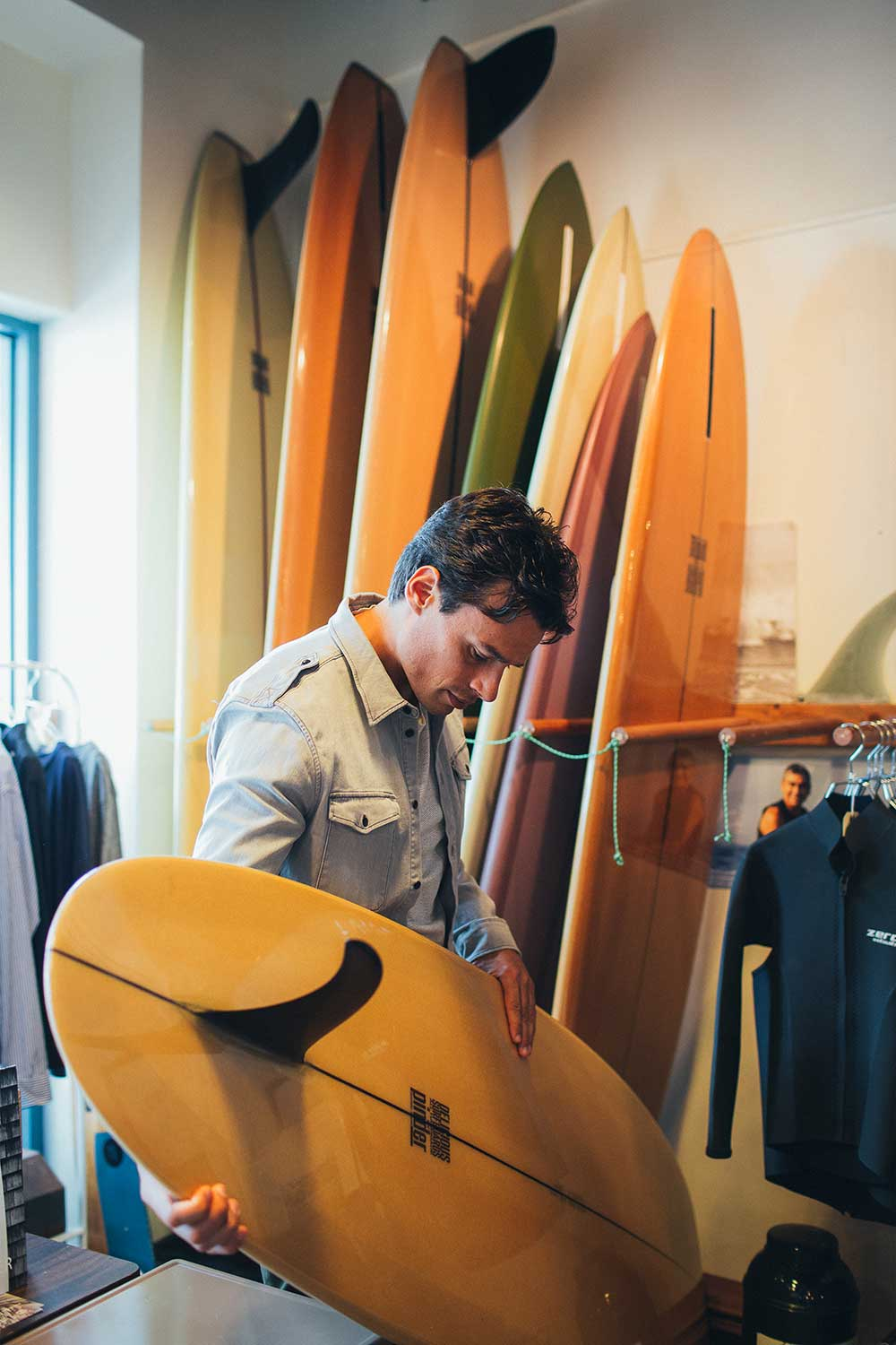 Man looking at assortment of wood surfboards