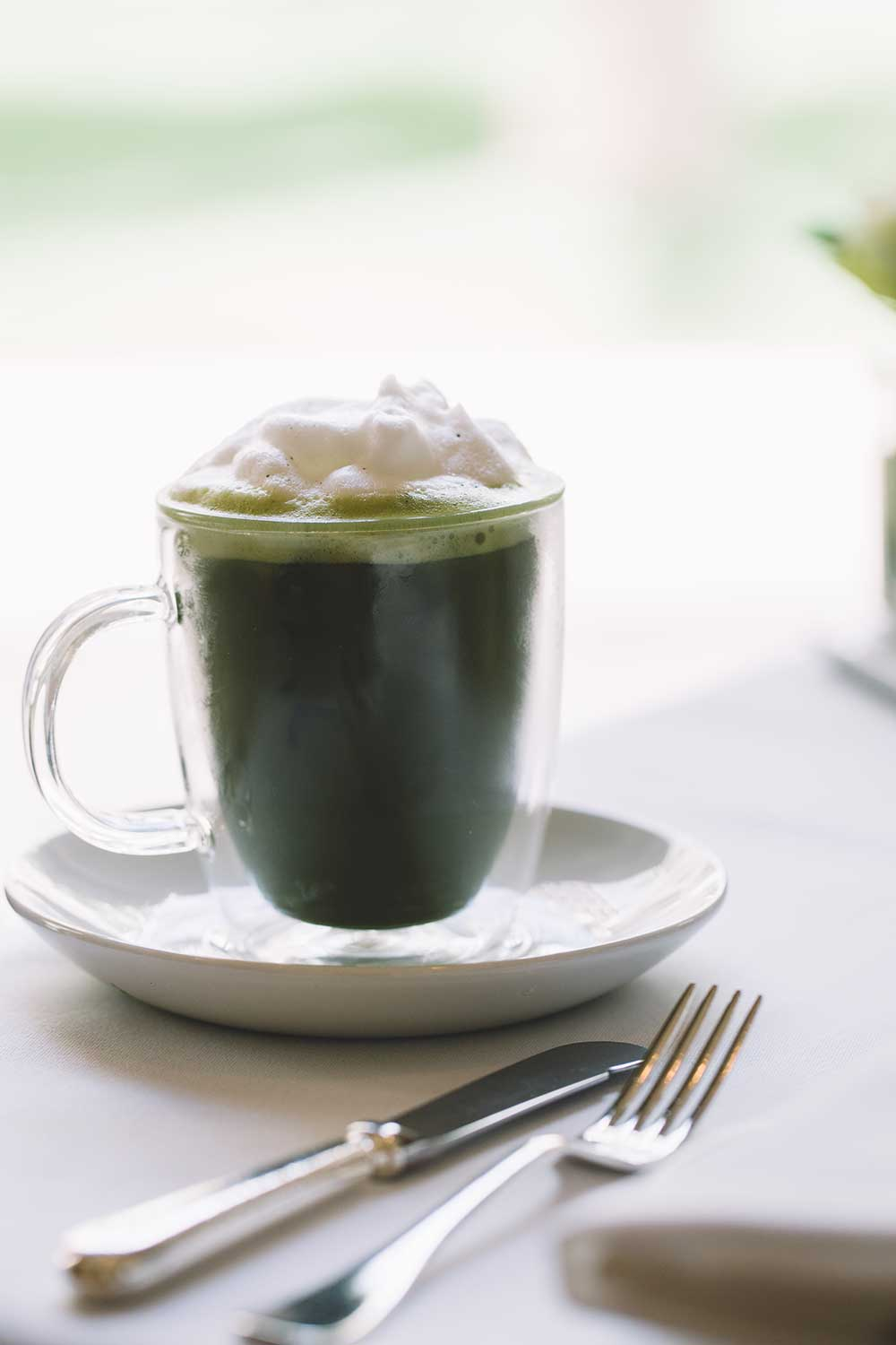 cup of Japanese tea with fresh whipped cream on table