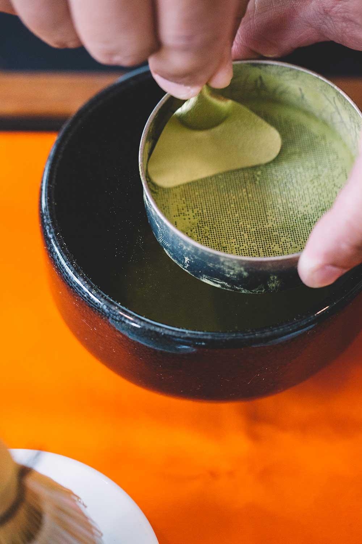 person sifting matcha tea