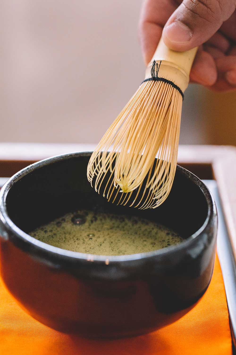 person stirring matcha tea with bamboo whisk