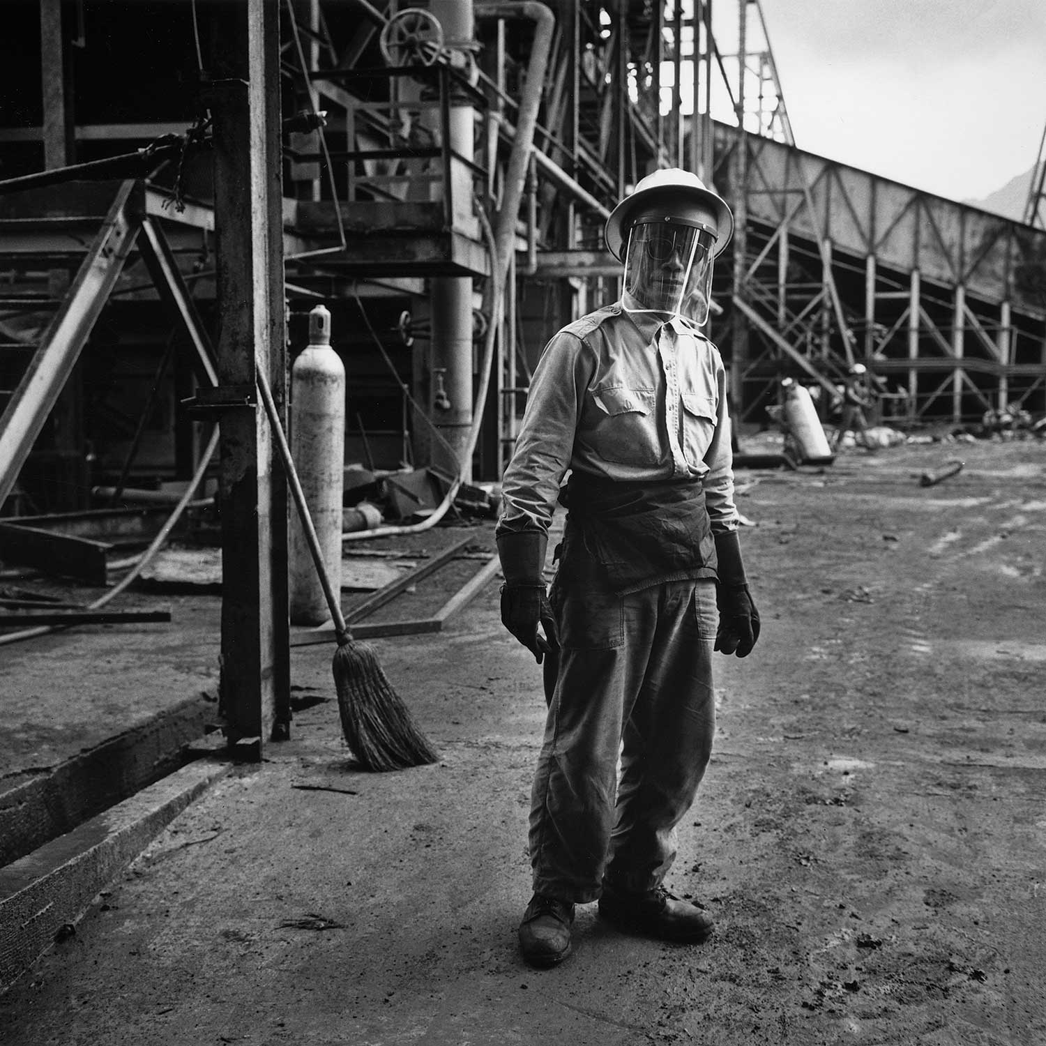 Black and white photograph of sugarcane worker at the mill