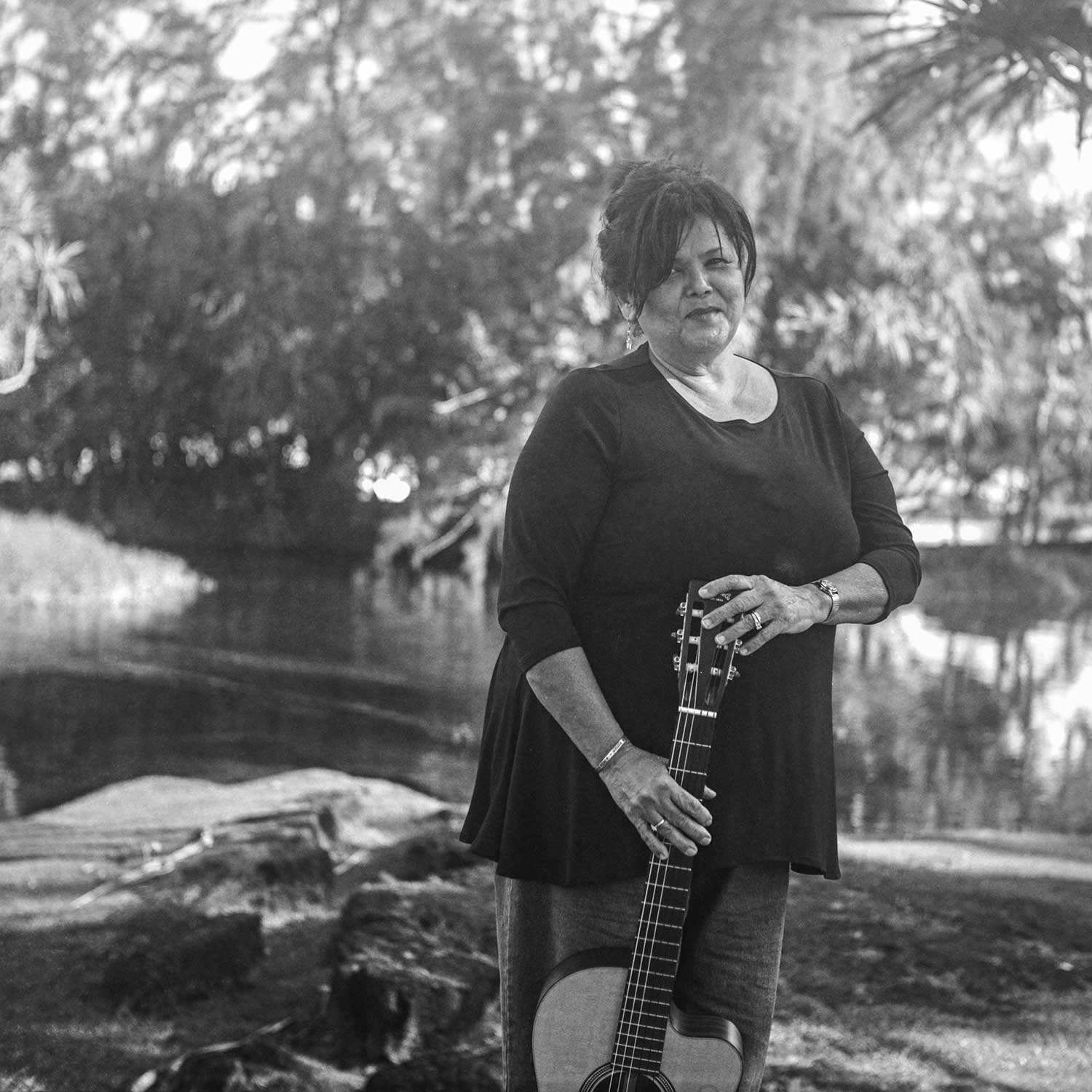 black and white photo of Alice Wise holding a guitar near water