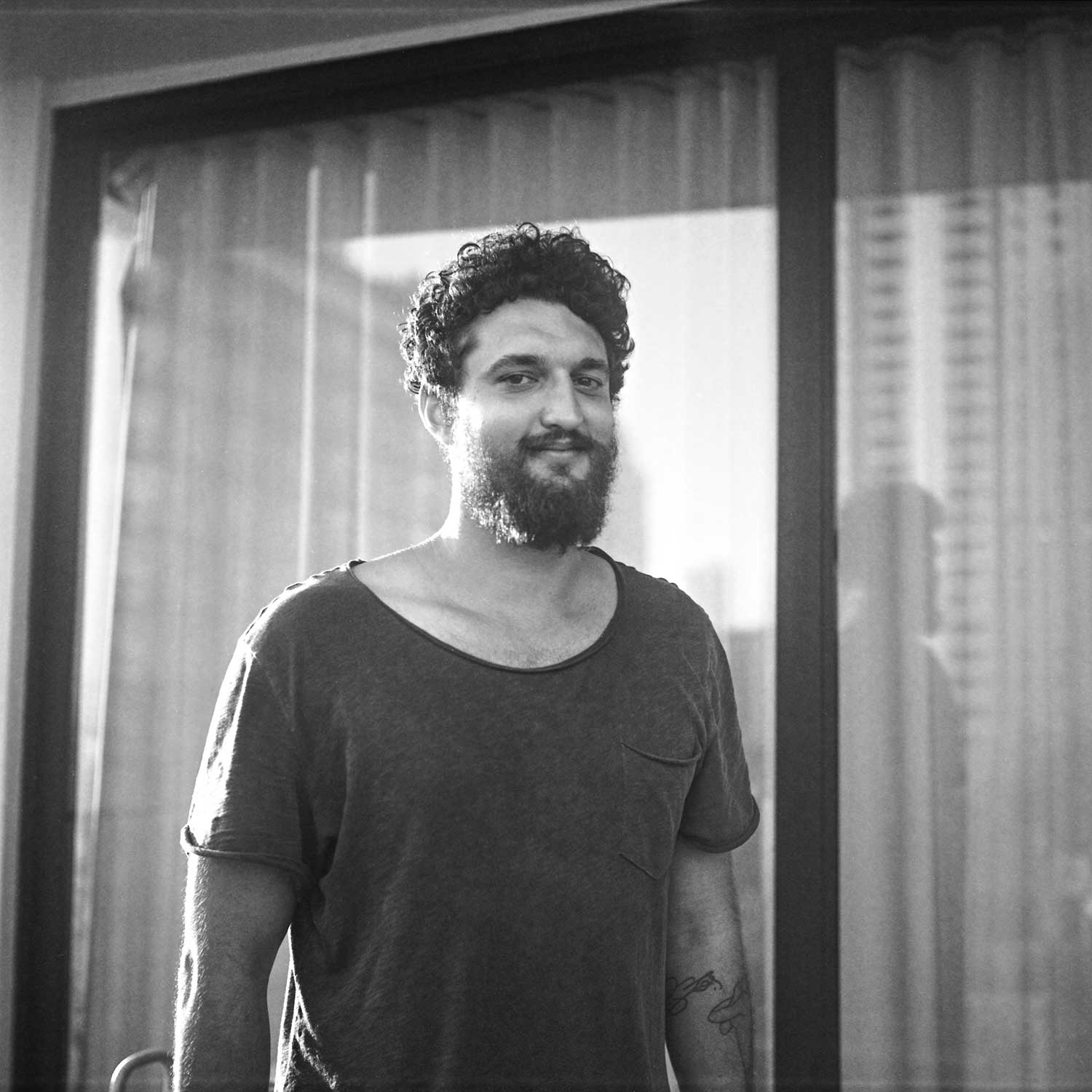 black and white photo of Assistant Producer Pedru Carvalho in front of glass door