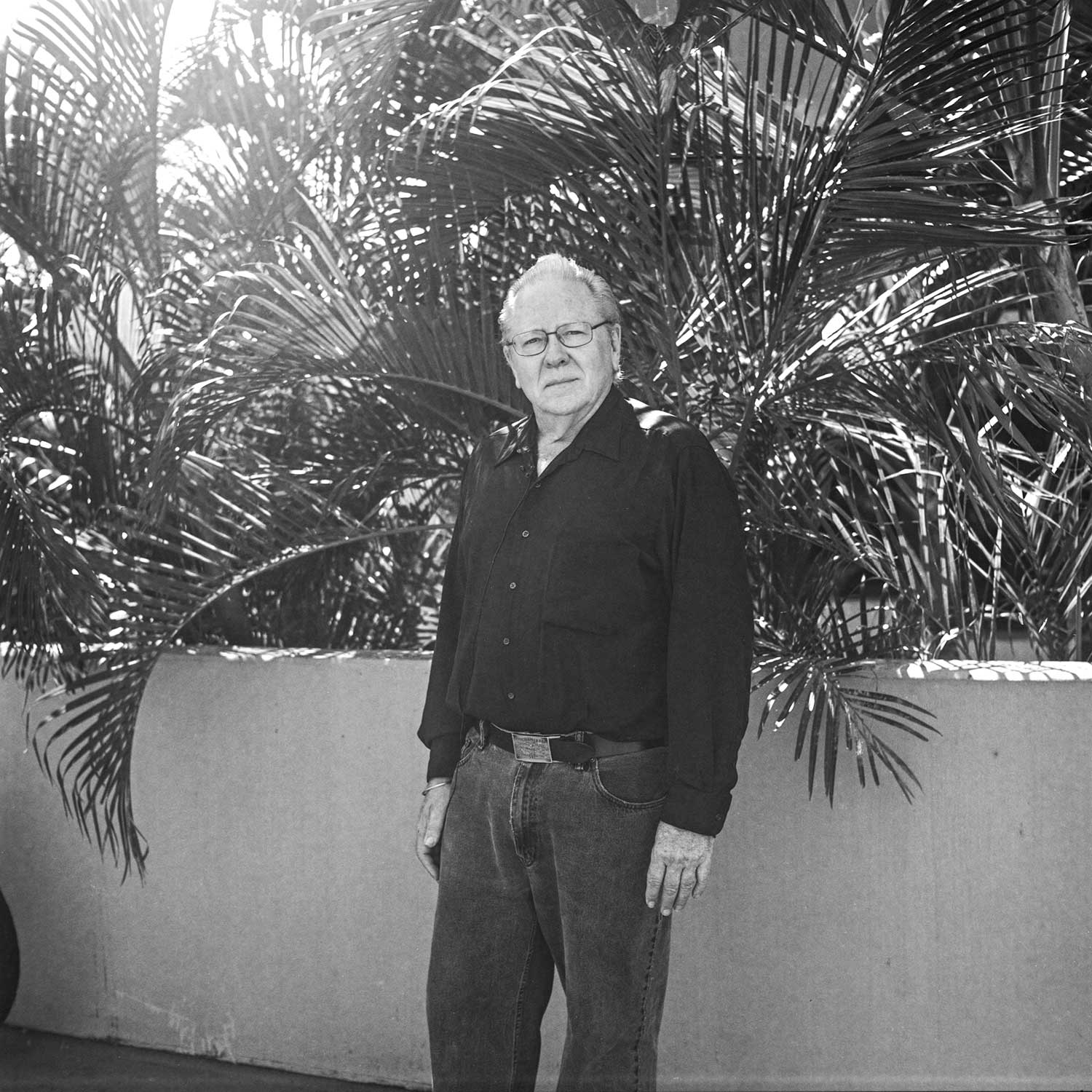 black and white photo of John Berger standing by wall with palms
