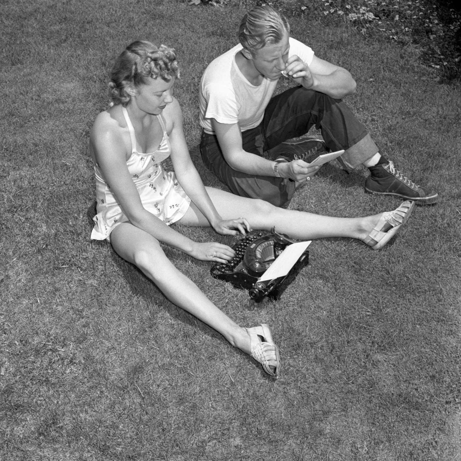 Black and white photo of man smoking and woman typing while sitting on the lawn