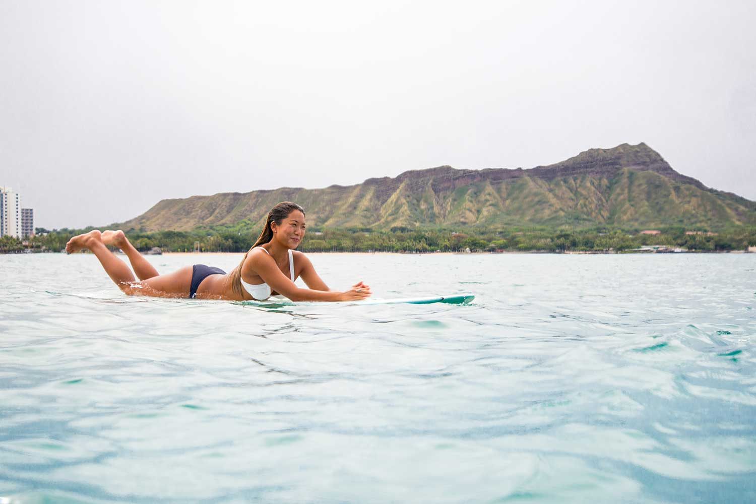 Nicolette Kim laying on surfboard in the ocean with Diamondhead in the background
