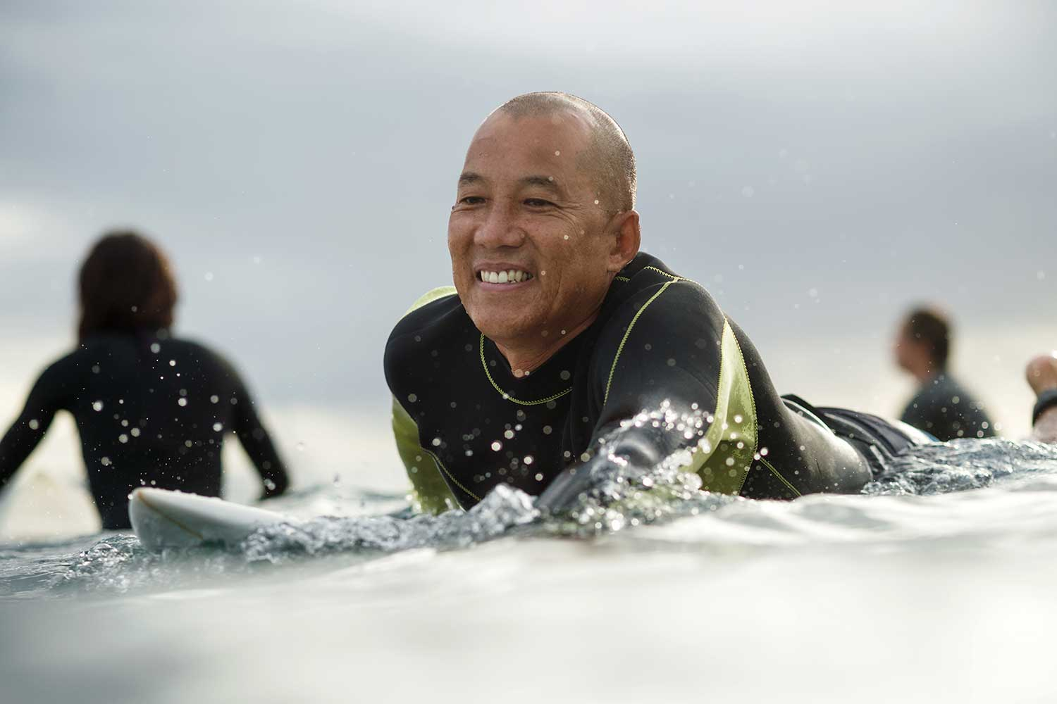 Guy Chang on surfboard in the ocean