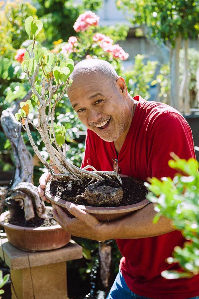 Kahi Ching in red shirt holding bonsai plant