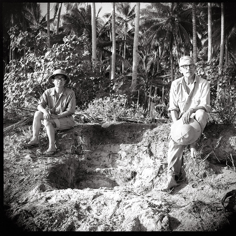 Black and white image of two men at an excavation site.