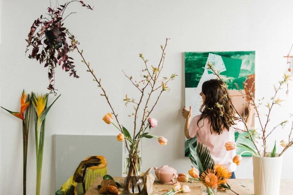 Hadley Nunes hanging artwork up in studio