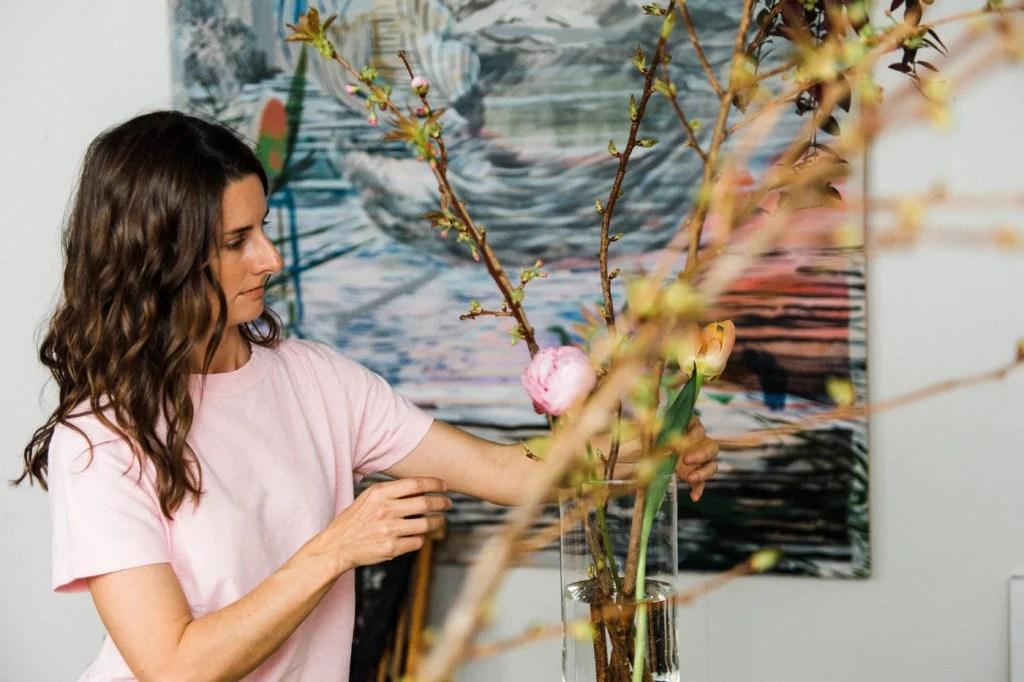 Hadley Nunes working in studio with flower arrangement.
