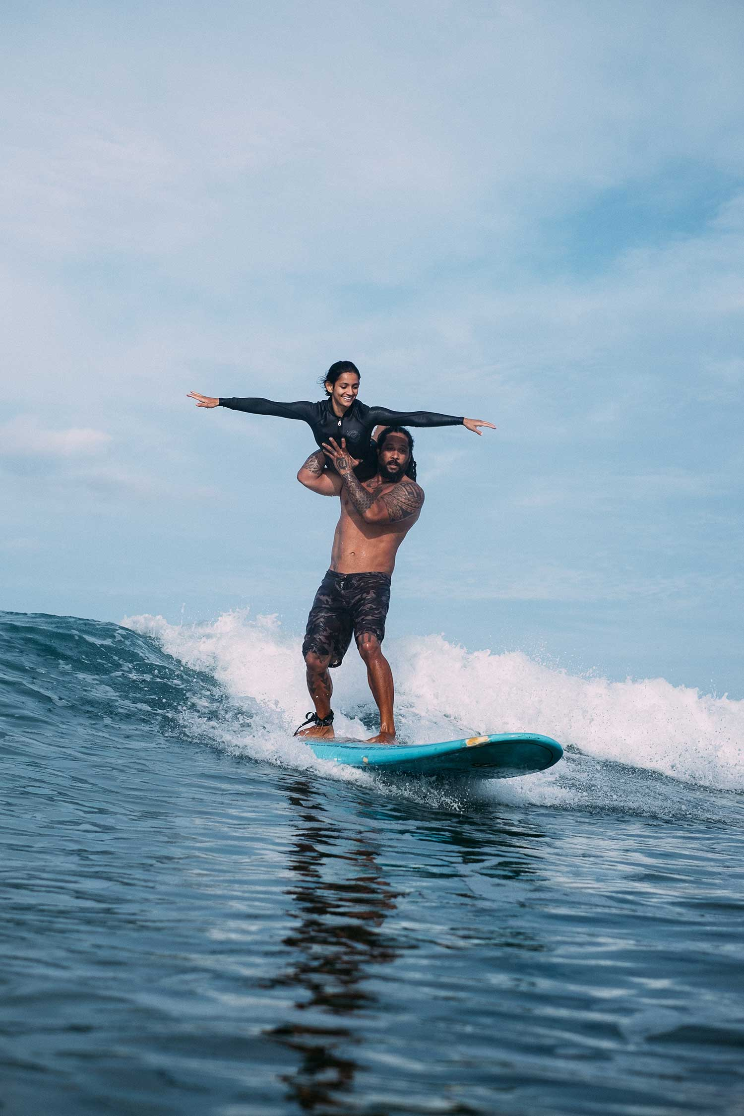 Tandem surfers doing tricks while catching waves