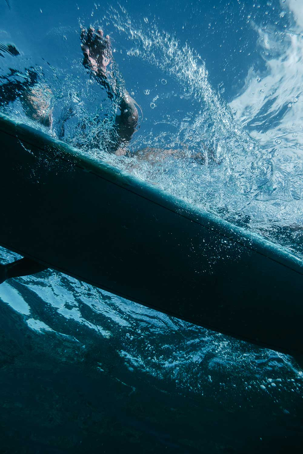 Underwater photo of a surf board and surfer paddling