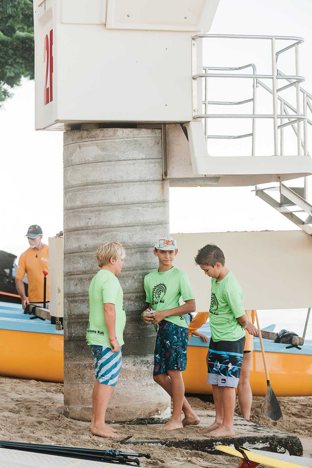 Three little boys in green shirts and board shorts stand by a life guard station