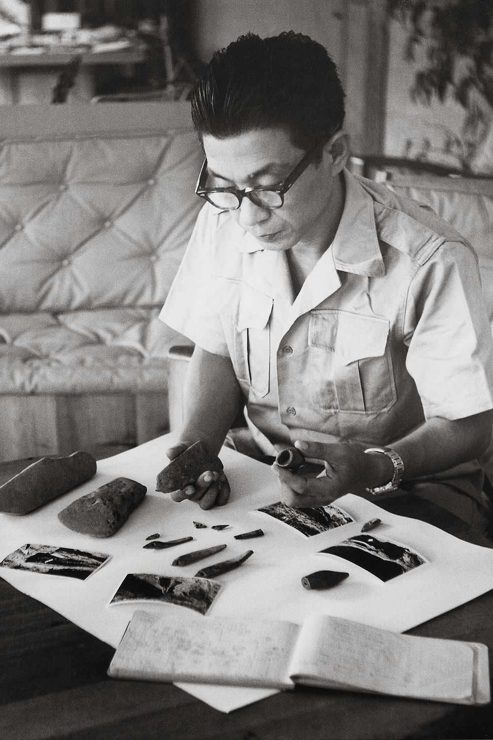 Black and white image of an asian man with glasses examining artifacts.