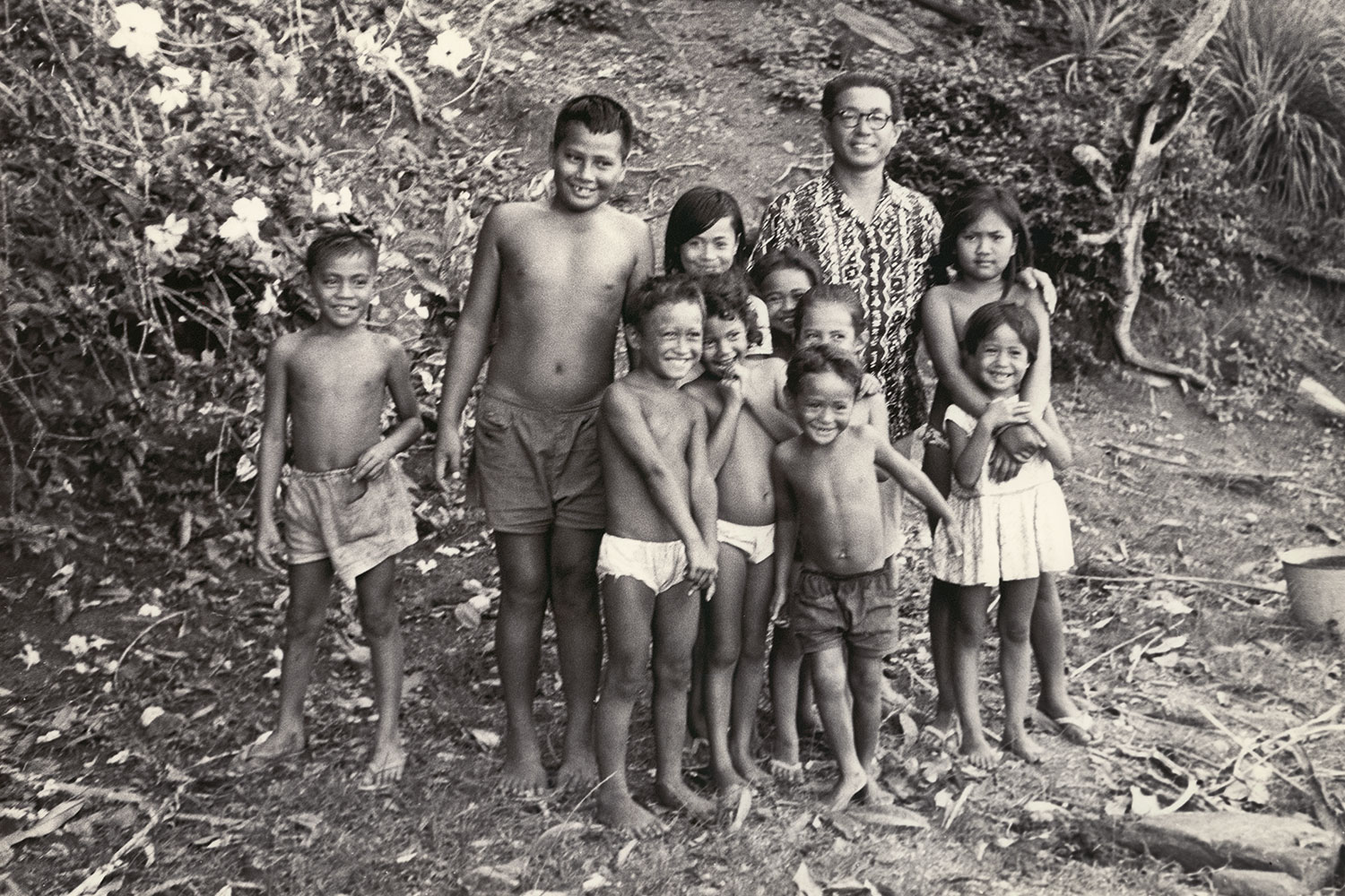 Black and white photo of a group of kids smiling for the camera.