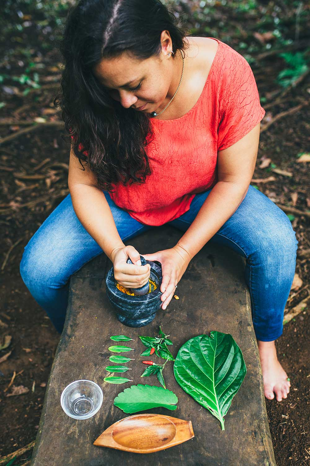 Woman in red shirt and jeans pounding a Hawaiian plant in a stone bowl.