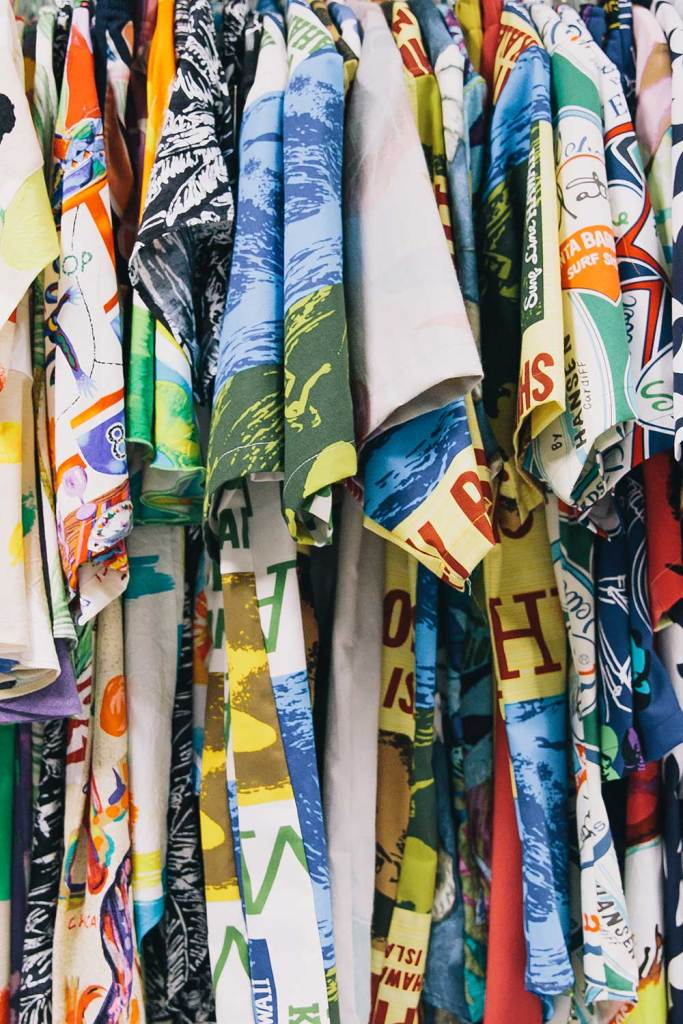 An assortment of aloha shirts hanging on a rack.