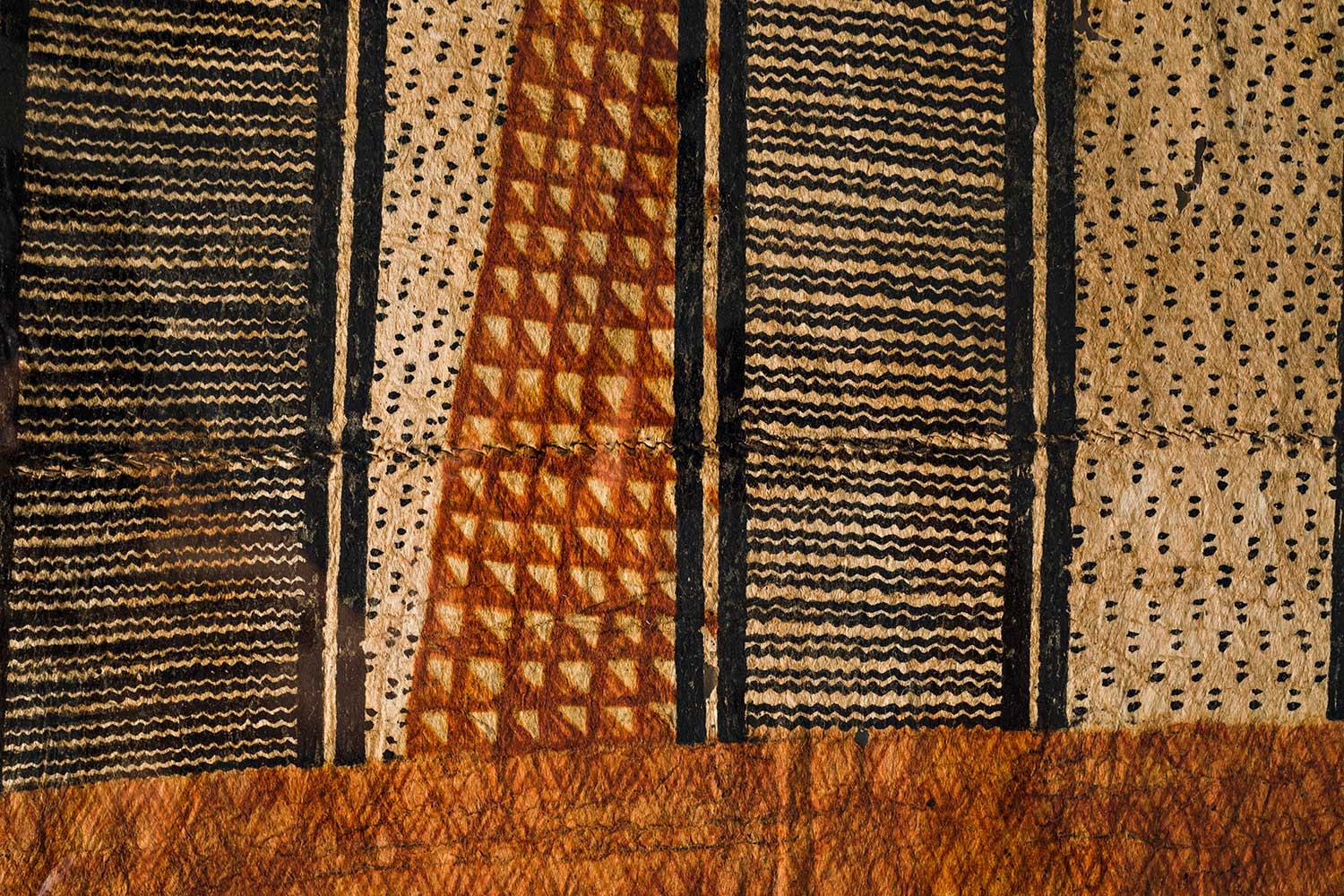 An ancient kapa cloth with black and brown design embedded into it.