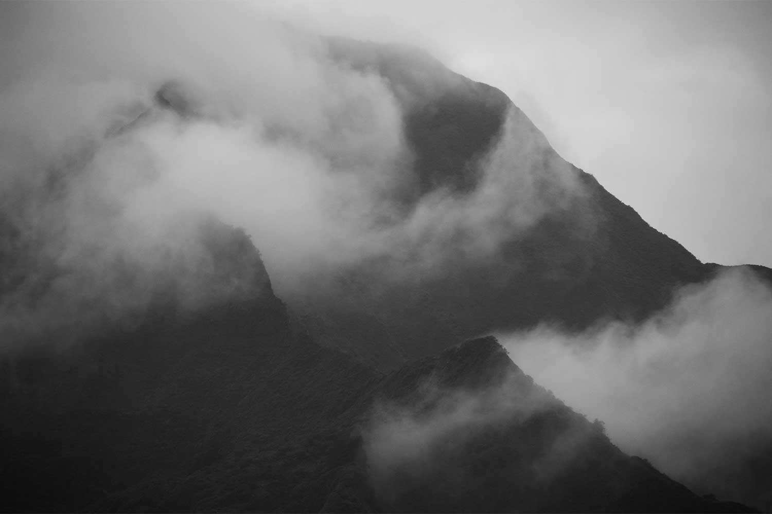 Black and white image of clouds covering a ridge in the Koolau mountain range