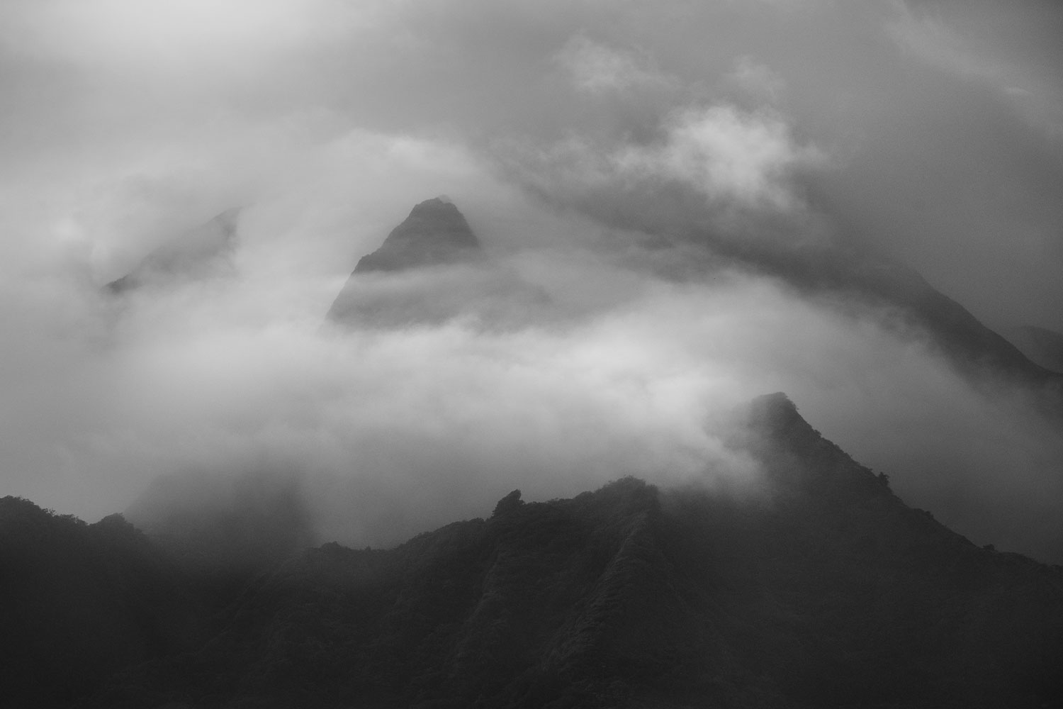 Black and white image of clouds blanketing the top of the Koolau mountain range