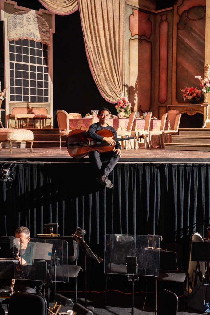 Man sitting on the edge of a stage holding a cello in front of an orchestra