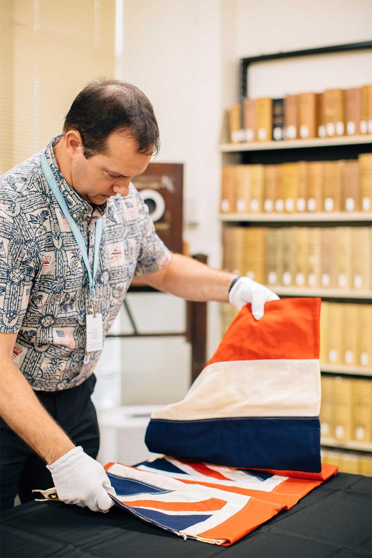 State archivist handling a Hawaiian flag
