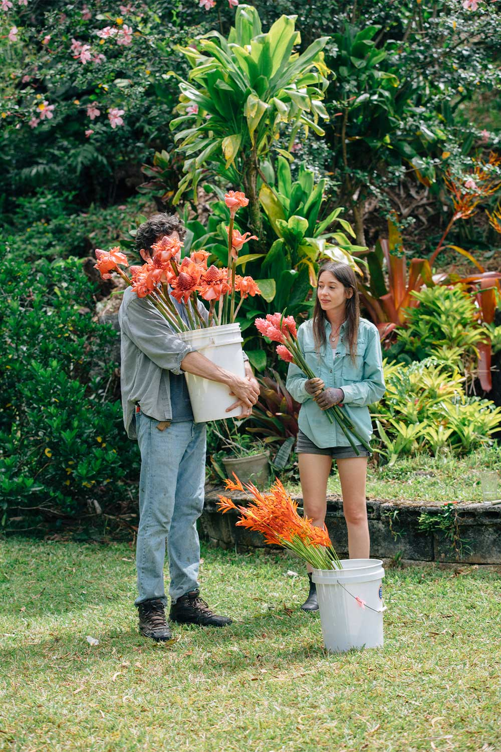 A man holding a bucket of flowers and woman placing in more flowers.