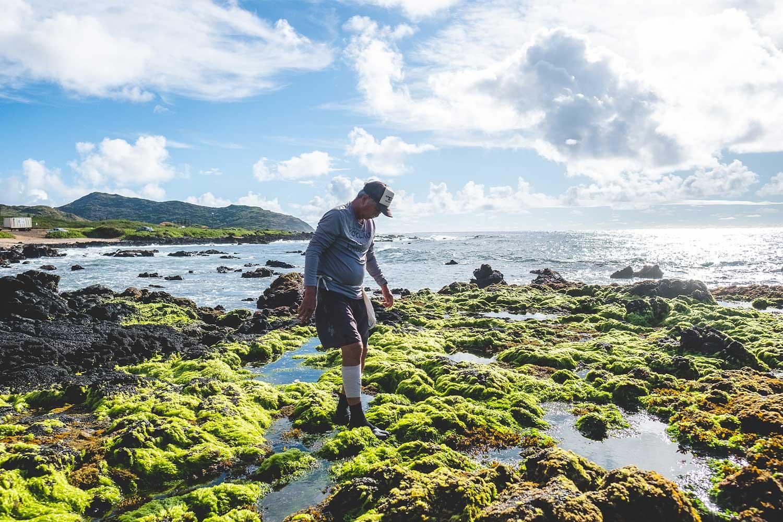 Man walking across moss covered rocks