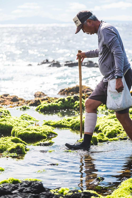 Man walking through water near the ocean's edge