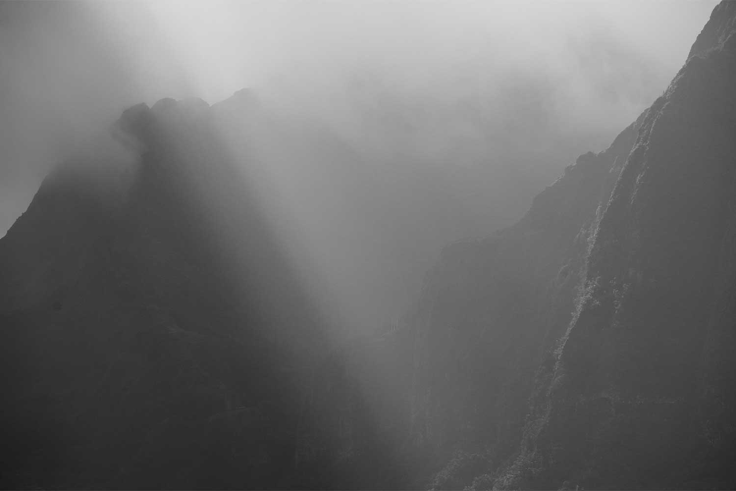 Black and white image of the Koolau mountain range with light shining through clouds