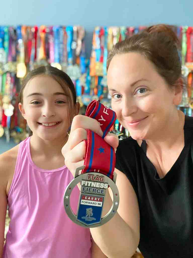mom and daughter with running medal