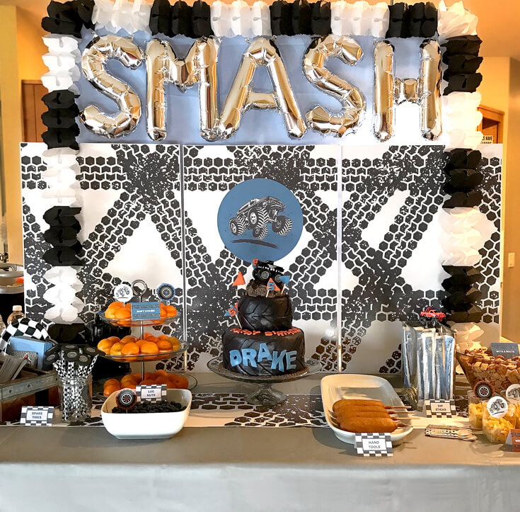 Great backdrop for a fun party. Easy to do with large photos, a table cover, letter balloons, and a tissue paper garland. Monster Truck Party Menu | Halfpint Design with Party Printables from HalfpintPartyDesign on Etsy. Boy party theme. 5th birthday. Boy theme.