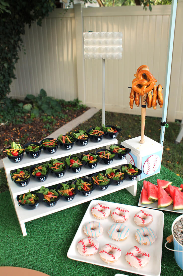 Salad served in mini baseball helmet displayed stadium style. Yankees Baseball Themed Baby Shower | Halfpint Design - boy baby shower theme, baseball party
