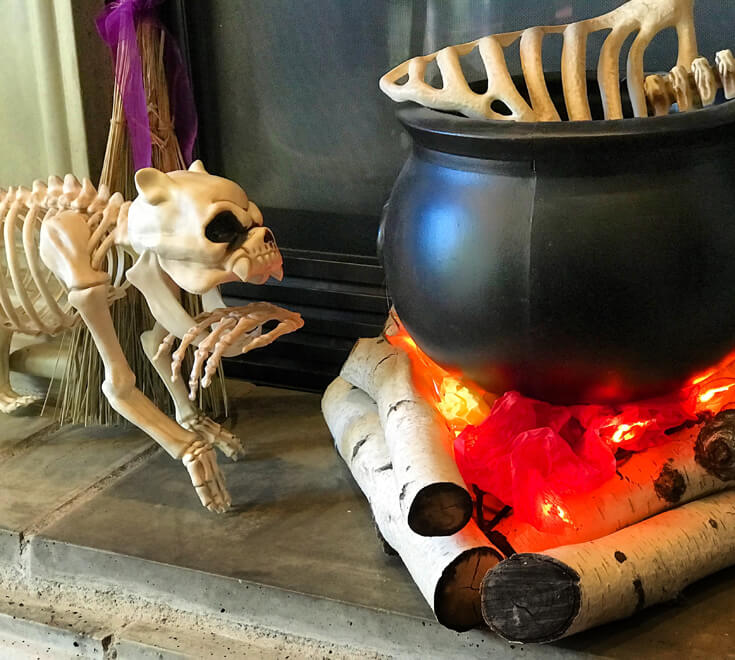 Want to make bone soup for Halloween? Create this super easy witches' cauldron with realistic flickering flames. Add bones for the finishing touch. Create an Eerie Witch's Cauldron   Halfpint Design - Halloween decorations, witch decor, faux fire, fake campfire, firelight bulbs