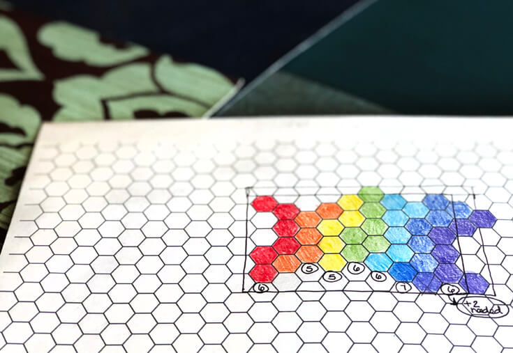 Sheet of hexagon paper used to lay out the design of a rainbow colored Art Party backdrop